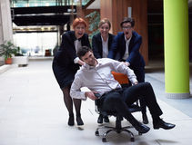 Business people group have fun. Business people group at modern office indoors have fun and push office chair on corridor Stock Photography
