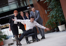 Business people group have fun. Business people group at modern office indoors have fun and push office chair on corridor Stock Images
