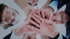 Business people group joining hands and representing concept of friendship and teamwork. Low angle view Royalty Free Stock Photos
