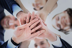 Business people group joining hands and representing concept of friendship and teamwork. Low angle view Royalty Free Stock Image