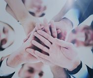 Business people group joining hands and representing concept of friendship and teamwork. Low angle view Stock Image