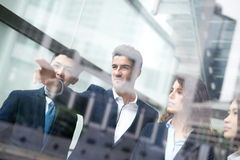 Business people group meeting. Pointing something in front of the office window, asian people,european Stock Images