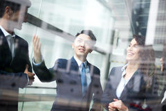 Business people group meeting. Pointing something in front of the office window, asian people,european Stock Photography
