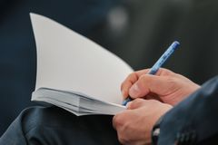 Business people hand in suit writing on notebook at lecture or seminar, close up Royalty Free Stock Photography