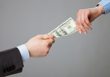 Business people hands exchanging money. Closeup shot on grey background stock photos