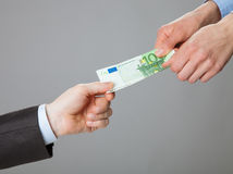 Business people hands exchanging money. Closeup shot on grey background stock image
