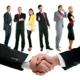 Business people handshake and company team. Business people handshake with company team in background Royalty Free Stock Image