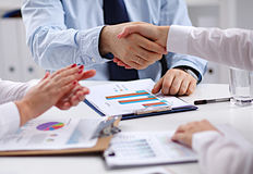 Business people handshake, sitting at the table.  Royalty Free Stock Images