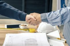 Business people handshaking at background over helmets, documents, worker tool. Close-up of business people handshaking at background over helmets, documents Stock Photo