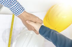 Business people handshaking at background over helmets, documents, worker tool. Close-up of business people handshaking at background over helmets, documents Stock Photography
