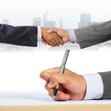 Business people handshaking. With document signing Stock Photos