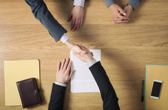 Business people handshaking after signing an agreement. Business people at office desk handshaking after signing an agreement, hands top view, unrecognizable Royalty Free Stock Image