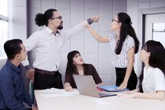 Business people having an argument in a group meeting. Asian business people pointing to each other having an argument in a group meeting stock photography