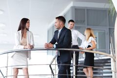Business people having break and talking on terrace of office building. Stock Photos
