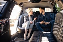 Business people having disccusion in limo. Usine Stock Photos