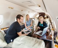 Business People Having Discussion On Private Jet. Business people having discussion over laptop on private jet Royalty Free Stock Image