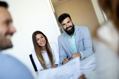 Business people having fun and chatting at workplace office. Young business people having fun and chatting at workplace office royalty free stock photography