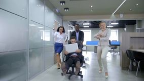 Business people having fun pushing their partners racing on office chairs .