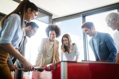 Business people having great time together.Colleagues playing table football in office. stock photos