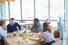 Business people having lunch at office cafeteria. High angle view of business people having lunch on table at office cafeteria royalty free stock photography