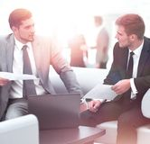 Business people Having Meeting Around Table In Modern Office. Image of business partners discussing documents and ideas at meeting Stock Image