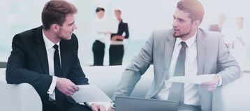 Business people Having Meeting Around Table In Modern Office. Image of business partners discussing documents and ideas at meeting Royalty Free Stock Photography