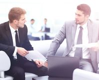 Business people Having Meeting Around Table In Modern Office. Image of business partners discussing documents and ideas at meeting Stock Images