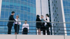Business people having a meeting outdoors on the terrace. They greet each other and begin conversation stock video footage