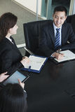 Business people having meeting, sitting at conference table Stock Photos