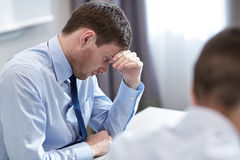 Business people having problem in office. Business, teamwork, people and crisis concept - business team sitting sad and solving problem in office Stock Photos