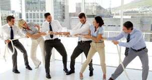 Business people having a tug of war stock footage