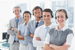 Business people with headsets smiling at camera Stock Photos