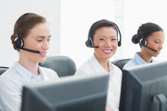 Business people with headsets smiling at camera Royalty Free Stock Photography
