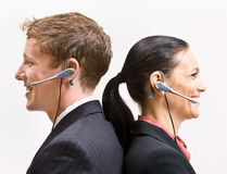 Business people in headsets standing back to back.  Stock Image