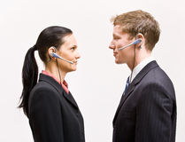 Business people in headsets standing face to face. Two business people in headsets standing face to face Stock Photo