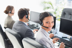 Business people with headsets using computers Stock Image
