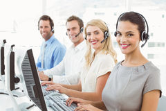 Business people with headsets using computers in office Stock Photos