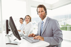 Business people with headsets using computers in office Stock Image