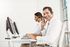 Business people with headsets using computers in office Royalty Free Stock Photography