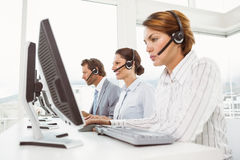 Business people with headsets using computers in office Royalty Free Stock Images