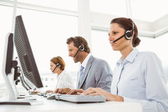 Business people with headsets using computers in office Stock Photography