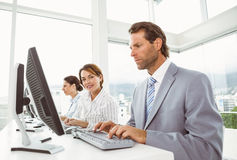 Business people with headsets using computers in office Royalty Free Stock Photos