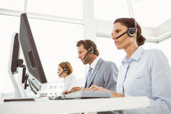 Business people with headsets using computers in office Stock Images