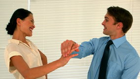 Business people high fiving in the staff room. In slow motion stock footage