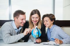 Business people hold little office globe and point at it Stock Images