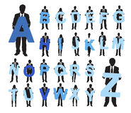 Business People Holding Alphabet Texts. Silhouettes of Business People Holding Alphabet Texts Stock Photography