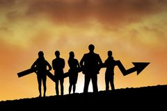 Business people holding an arrow silhouette against sunset or sunrise Stock Photos