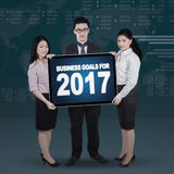 Business people holding billboard with 2017. Full length of business people holding a billboard with text of business goals for 2017 royalty free stock photos
