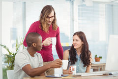 Business people holding coffee cups while working at computer desk Royalty Free Stock Photo
