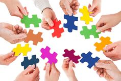 Business people holding colorful jigsaw pieces. Cropped image of business people holding colorful jigsaw pieces over white background Royalty Free Stock Photography